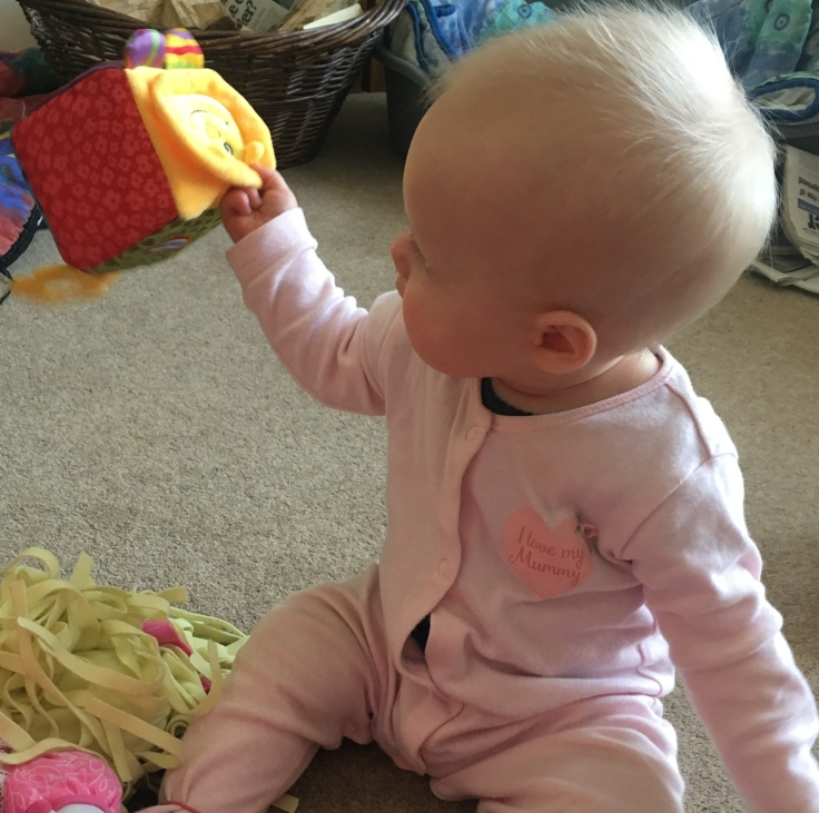 Sitting up, playing with her toys